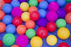 Colorful plastic balls on blue background. Stock Photos