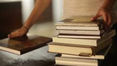 Woman puts stack of books on the table - stock footage