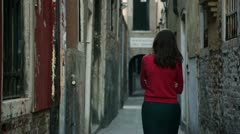 Young girl walks through the narrow streets of Venice - stock footage