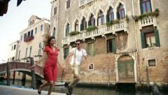 Boy and girl running beside the river in Venice - stock footage