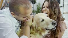 Young couple, relaxing at home and cuddling their pet dog Stock Footage