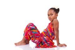 cute young african asian girl seated on the floor - stock photo