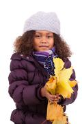 little african asian girl wearing winter clothes playing with leaf trees - stock photo