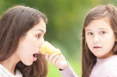 daughter poked mother with ice cream in her face. - stock photo