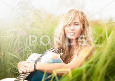 Stock photo of beautiful woman with guitar sitting on grass.
