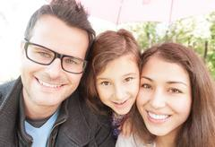 Close up portrait of happy family of three. Stock Photos
