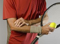 Tennis player massaging elbow Stock Photos