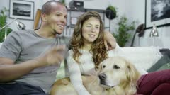 Cosy on the sofa at home, a young couple and their dog Stock Footage