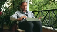 Successful, excited businessman with laptop sitting on his balcony Stock Footage