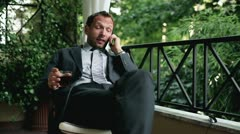 Young businessman with cellphone after hard work drinking whisky on his balcony Stock Footage