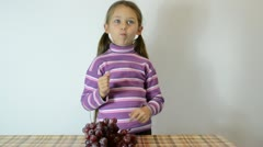 girl eating grapes taking berries from clusters lying on the table - stock footage