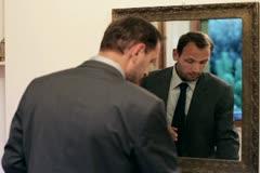 Businessman applying eye cream in front of mirror Stock Footage