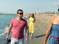 Young people walking on the beach with cellphone - stock footage