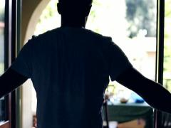 Young man opening doors and sitting on his terrace, slow motion Stock Footage