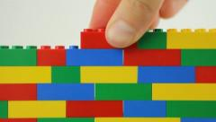 Hand adding blocks to lego wall Stock Footage