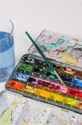 watercolor paint box with brush and water glass - stock photo