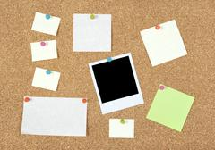 Post-it notes, papers and photo on a corkboard - stock photo