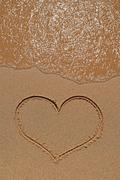 Heart drawing on sandy beach - stock photo