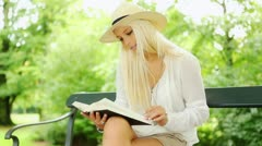 Woman reading a book in park - stock footage