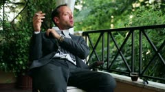 Young businessman after hard work drinking and smoking cigarette on his balcony Stock Footage