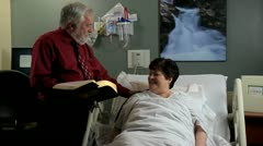 Stock Video Footage of minister reading bible to patient