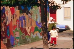 San Francisco, 1970's, Mission District murals, woman and child walk in front Stock Footage