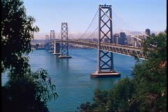 San Francisco, 1970's, The Bay Bridge, long wide shot, framed in trees, skyline Stock Footage