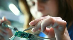Stock Video Footage of Female technician solders circuit board