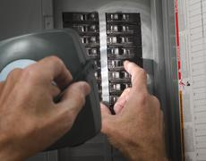 man with flashlight at residential circuit breaker panel - stock photo