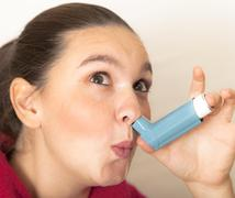 Smiling girl holds asthma inhalator against her nose - stock photo