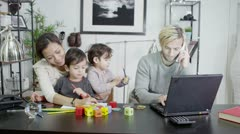 A busy father is working from home while his wife entertains their children - stock footage