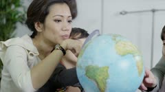 Attractive young parents using a globe to educate their children Stock Footage