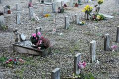 sad grave of a young child died and other sad gravestones - stock photo
