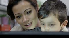 A mother teaches her young son how to use a computer Stock Footage
