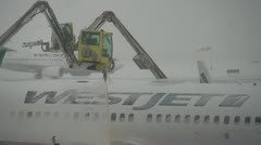 Aircraft de-icing during early winter storm, CU shot aircraft in bg Stock Footage