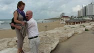 Couple play on a coastal tourist path Stock Footage