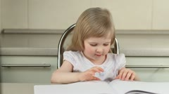 Lovely little girl turning over pages in album Stock Footage