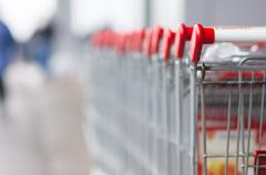 row of shopping carts near entrance of supermarket - stock photo