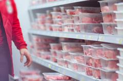 Customers selecting beef and pork slices on shelves in supermarket Stock Photos