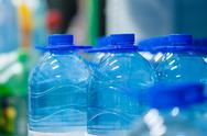 Stock Photo of blue bottles of fresh water in supermarket