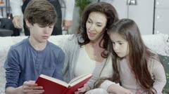 Young boy reads aloud to his parents and his sister at home Stock Footage