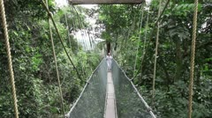 Woman walking on rainforest canopy walkway Stock Footage