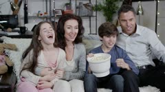 Happy family watching sports on t.v. and spilling popcorn everywhere - stock footage