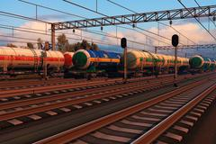 Freight trains with fuel tank cars in sunset - stock illustration