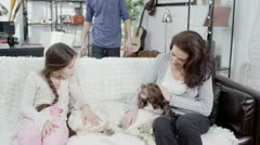 A mother and her children stroking the family dog on the sofa Stock Footage