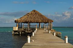Beach deck with palapa floating in the water Stock Photos