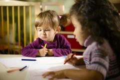 Children and fun, two preschoolers drawing in kindergarten Stock Photos