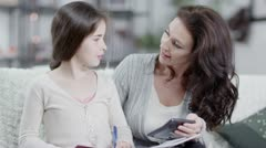 Mother and daughter doing homework together Stock Footage