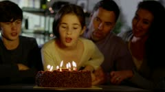 Young girl blows out the candles on her birthday cake Stock Footage