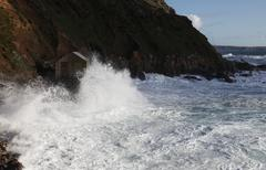 fishing hut being battered by waves - stock photo